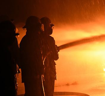 Emergency Management fire crew with a hose spraying